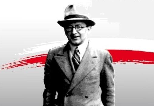 Marian Rejewski w kadrze od pasa w górę na tle barw narodowych.