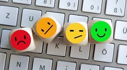 Buźki (emotikony) ułożone na klawiaturze komputerowej.