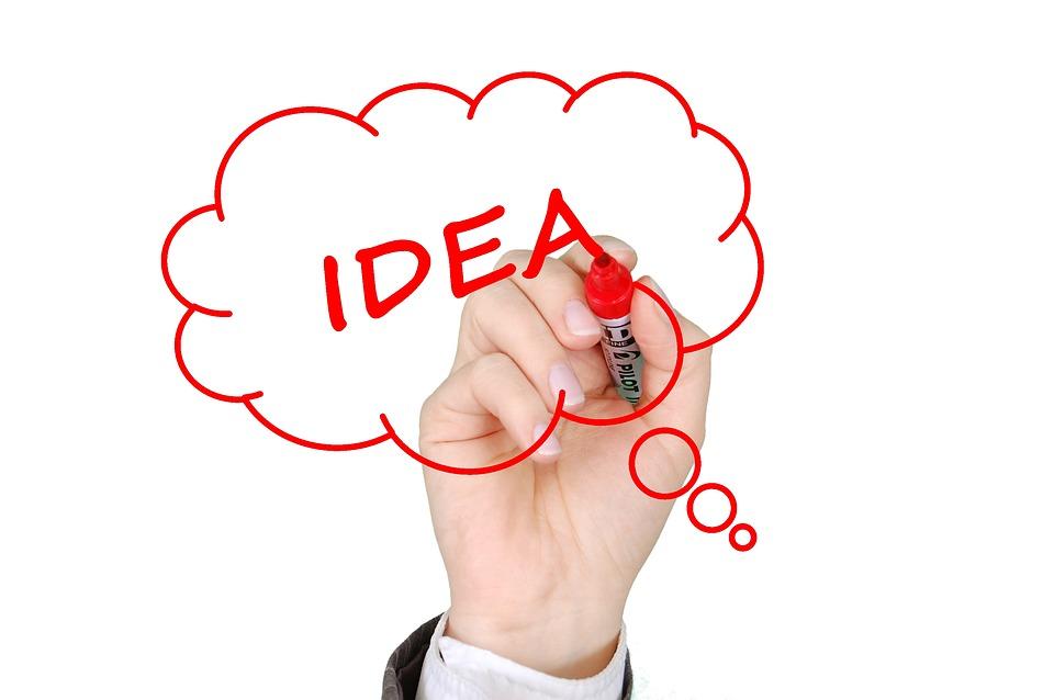 Dłoń z czerwonym flamastrem zapisująca słowo IDEA w dymku