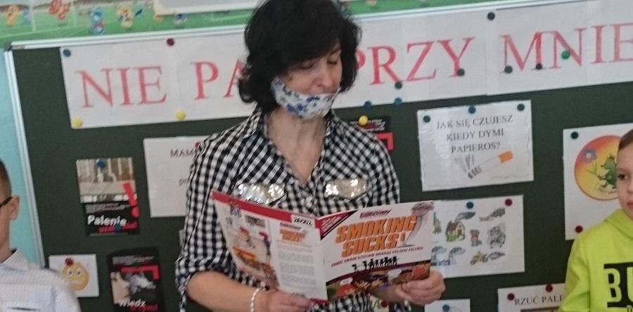 Bibliotekarka w maseczce na twarzy czyta książkę przedszkolakom.