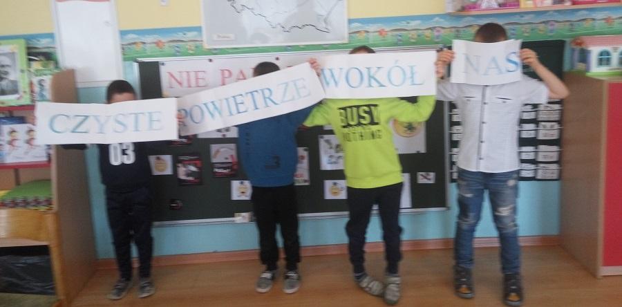 """Czterech przedszkolaków z uniesionymi kartami tworzącymi napis: """"Czyste powietrze wokół nas""""."""