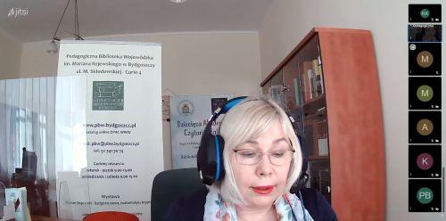 Dyrektor Ewa Pronobis-Sosnowska w słuchawkach z mikrofonem na tle regału z książkami i banerów Pedagogicznej Biblioteki Wojewódzkiej w Bydgoszczy.