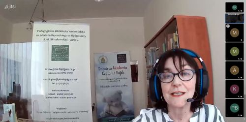 Zrzut ekranu z seminarium online: prelegentka Ewa Bedełek w słuchawkach z mikrofonem na tle regału z książkami i banerów bibliotecznych.