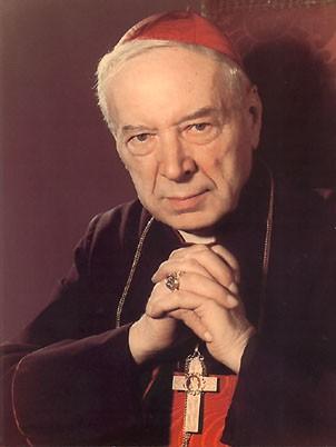 Ksiądz Stefan Wyszyński w kardynalskim stroju z dłońmi splecionymi do modlitwy pod brodą. Na piersi zawieszony krzyż, na palcu pierścień biskupi.