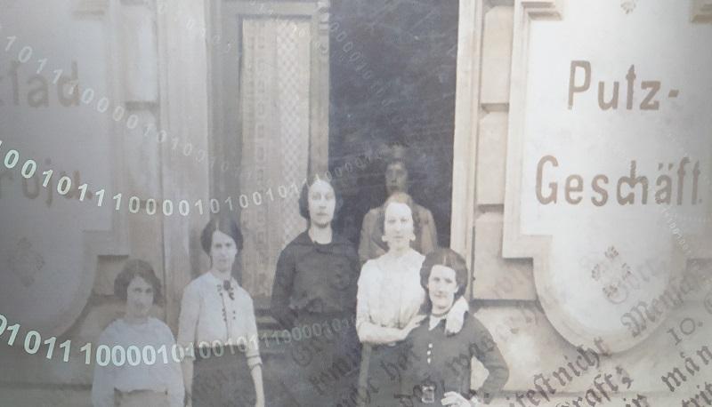 """Fragment planszy przedstawiający 6 kobiet przed budynkiem z szyldem """"Putz-Geschäft"""""""