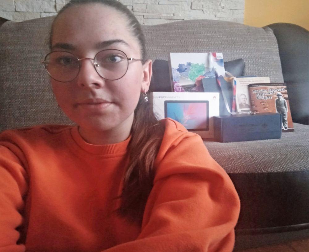 Nastolatka w okularach. W tle rozłożone na kanapie zdobyte nagrody.