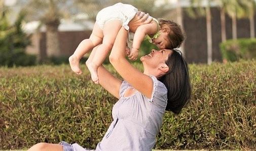 Matka unosząca niemowlaka nad głową.