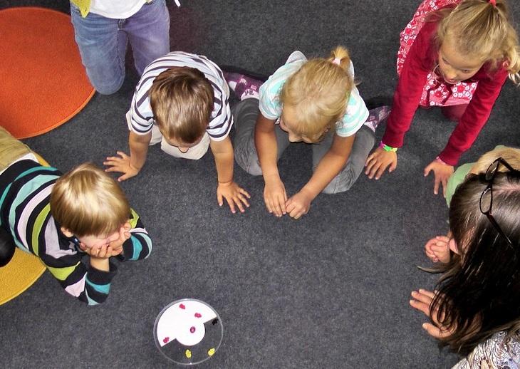 Kilkoro dzieci w wieku przedszkolnym zebranych wokół zabawki leżącej na podłodze.