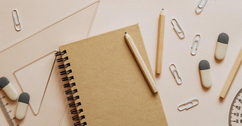 Na blacie biurka leżą ekierka, kątomierz, notatnik i ołówki.