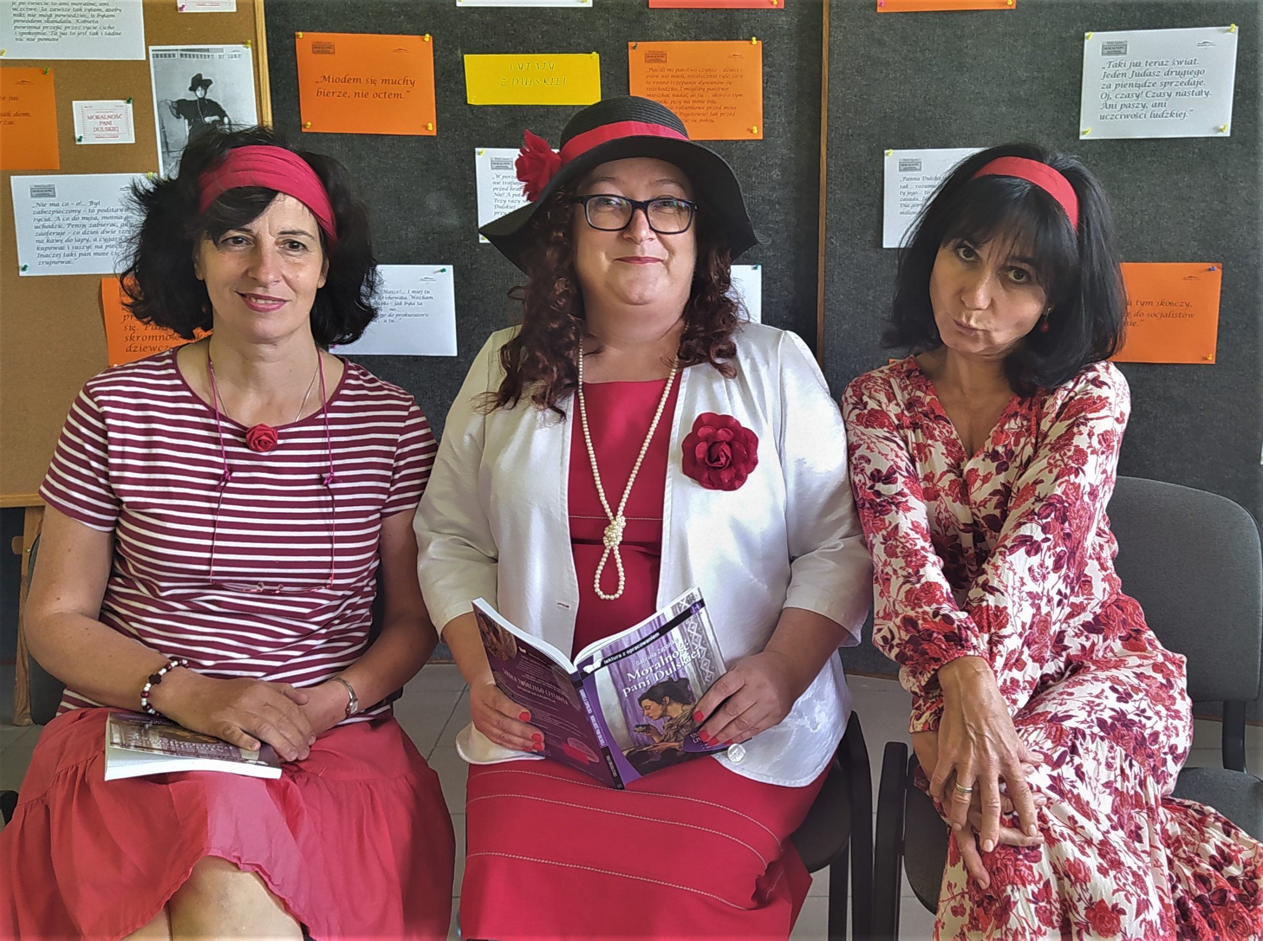 """Trzy kobiety ubrane w tonacji czerwieni i bieli. Środkowa postać w kapeluszu i z otwartym egzemplarzem książki """"Moralność pani Dulskiej""""."""