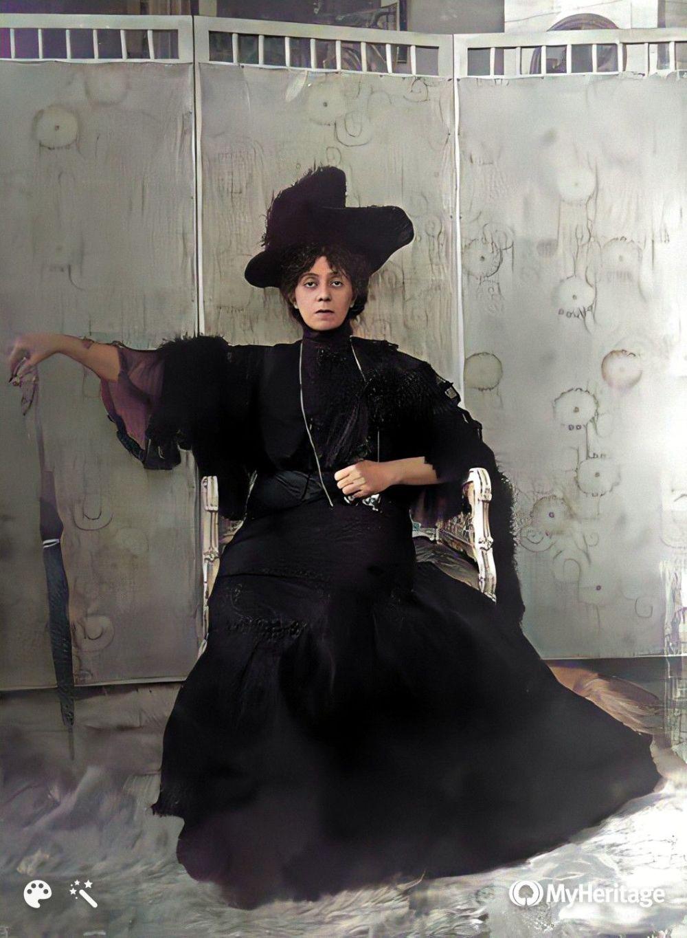 Gabriela Zapolska siedzi w fotelu w długiej sukni i kapeluszu, w wyprostowanej ręce trzyma parasolkę. W tle ozdobny parawan.