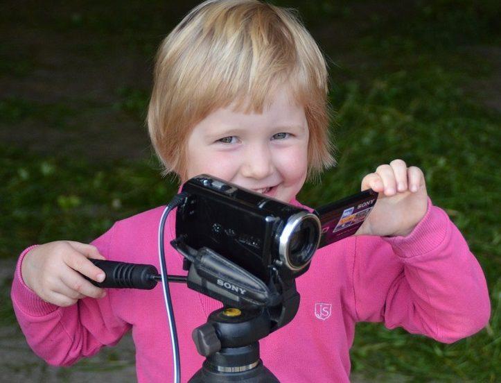Dziewczynka w wiku przedszkolnym trzyma kamerę ustawioną na statywie.