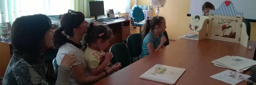 Dzieci bawią się w teatrzyk kamishibai w bibliotece.