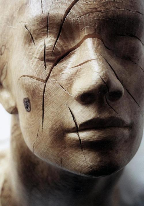 Rzeżba w drewnie przedstawiająca twarz kobiety z zamkniętymi oczami i z wyraźnymi pęknięciami podobnymi do ran..