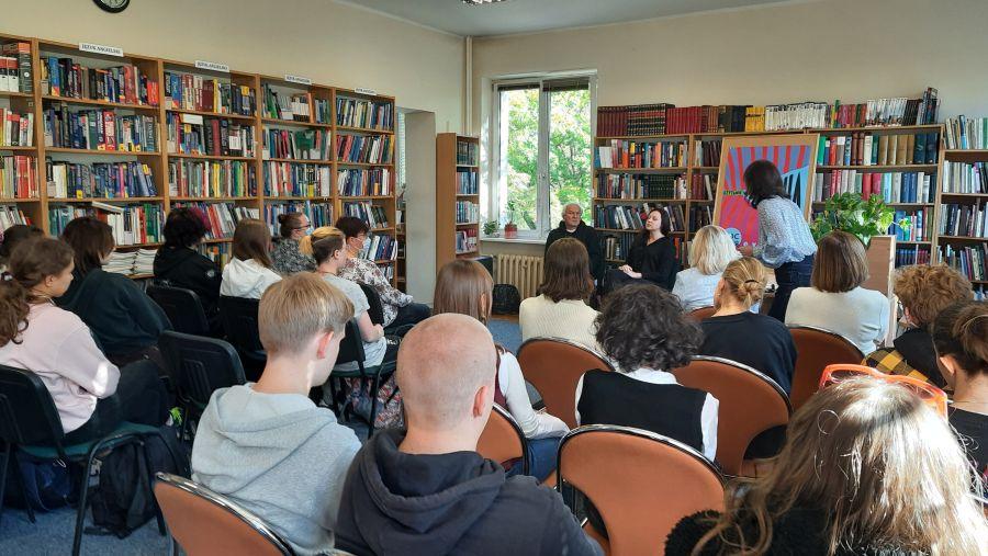 Młodzież na spotkaniu z młodą autorką w otoczeniu regałów z książkami.