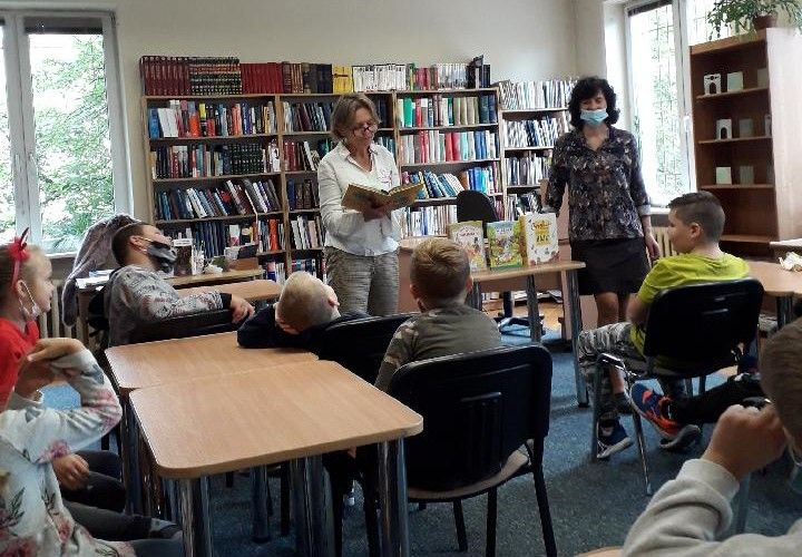 Dzieci w bibliotece słuchają bajek. Bibliotekarki na tle regałów z książkami.
