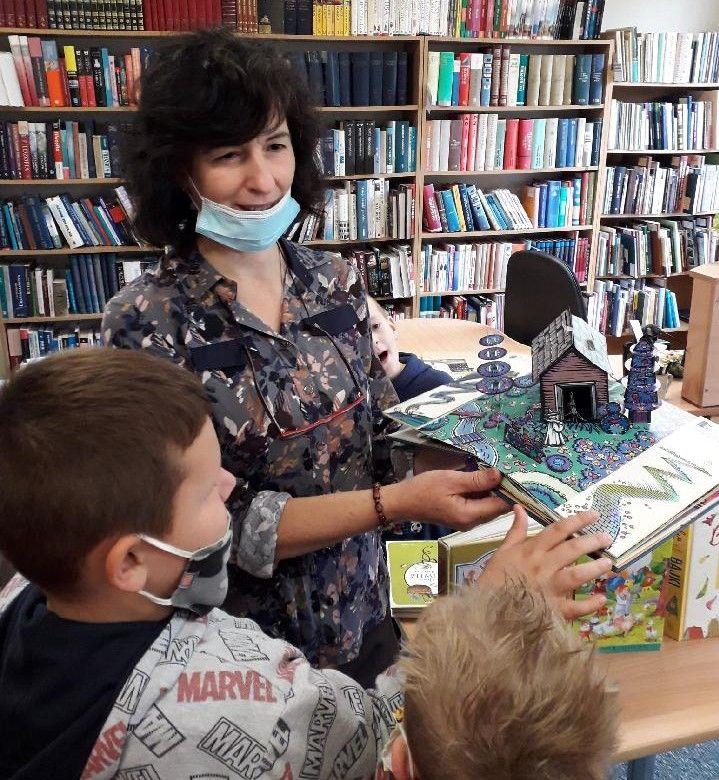 Bibliotekarka na tle regałów z książkami prezentuje 2 chłopcom książkę pop-up (z ruchomymi elementami).