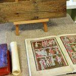 Książka otwarta na średniowiecznych ilustracjach. Powyżej deska z wyrytymi niewyraźnymi napisami.