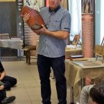 Autor wystawy przemawia do zwiedzającej wystawę młodzieży.