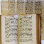 Otwarta księga ze średniowieczną czcionką. W tle strona z czterema szpaltami druku.