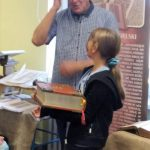 Jarosław Gaudek i dziewczynka trzymająca wielką księgę.