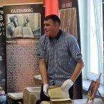 Jarosław Gaudek w białych rękawiczkach prezentuje stary egzemplarz Biblii.