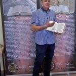 """Autor wystawy na tle banerów """"Biblia Wujka"""" i Biblia brzeska"""""""