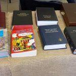 Prezentacja wydań Biblii z różnobarwnymi okładkami.