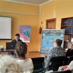 Leśnik prezentuje uczestnikom spotkania w bibliotece prezentację multimedialną na ekranie.